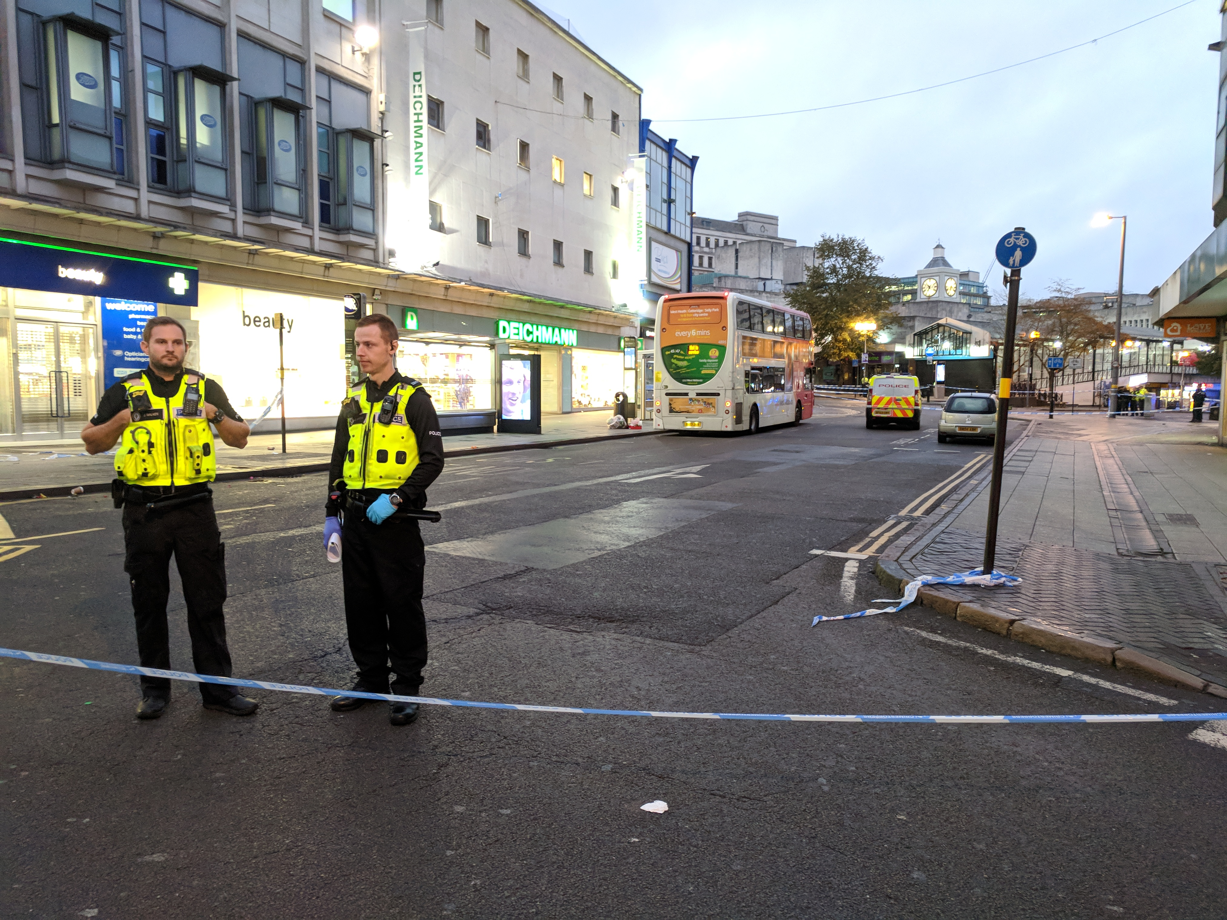 Area sealed off with police tape with two officers standing guard